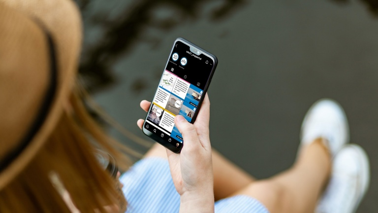 A woman looks at the SDE21 Instagram page on her smartphone