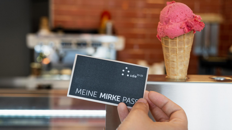 """A person redeems the voucher from the """"Mirke Pass"""" for a free cup of icecream"""